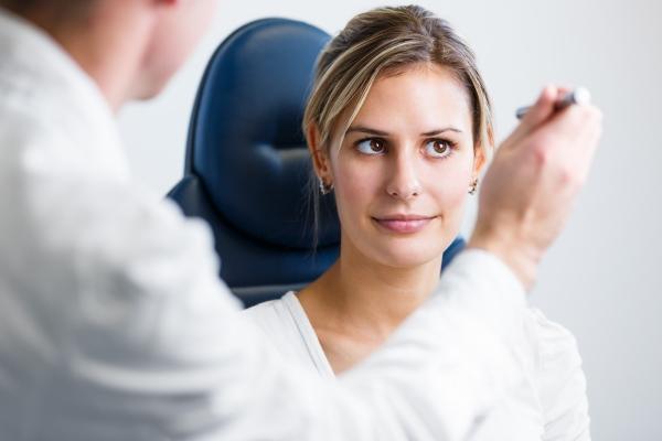 Офтальмолог смотрит глаза девушке